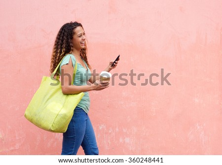 Side portrait of cheerful woman texting while walking with a cup of coffee, outdoors. - stock photo