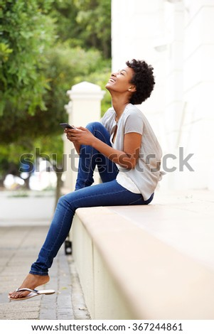 Side portrait of happy young woman sitting by a street with a mobile phone   - stock photo