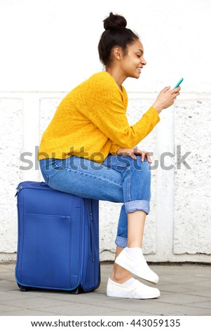 Side portrait of relaxed young woman sitting on suitcase and reading text message on her cell phone - stock photo