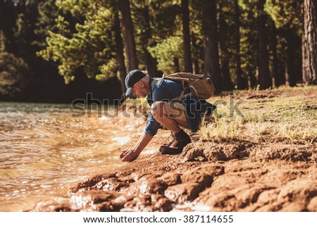 Side portrait of senior male hiker sitting by a lake and putting hands in water. Mature man washing face in lake.