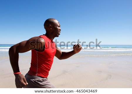 Side portrait of young african american man sprinting on the beach