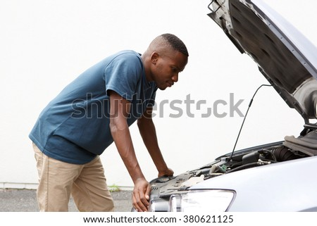 Side portrait of young african man looking under the hood of car - stock photo