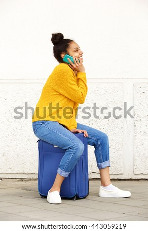 Side portrait of young african woman sitting on suitcase and making phone call - stock photo