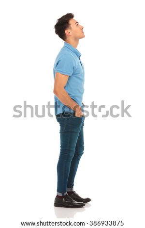 side portrait of young man in blue shirt looking up with hands in pockets while posing in isolated studio background - stock photo