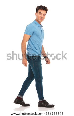 side portrait of young man in blue shirt walking in isolated studio background, looking at the camera  - stock photo