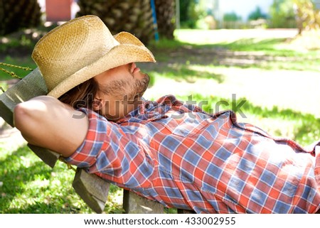 Side portrait of young man lying on hammock resting with cowboy hat - stock photo