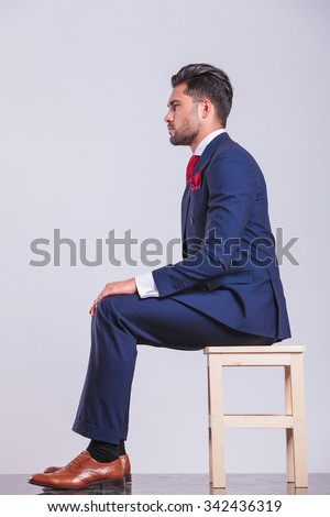 side portrait on man in suit sitting in studio with hands on his knees - stock photo