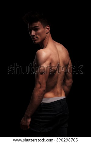 side portrait on standing muscular topless man, turning and posing for the camera in dark studio background
