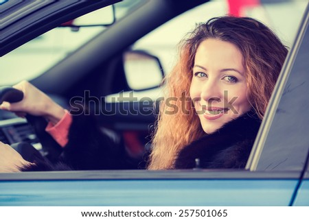 Side portrait smiling attractive happy winter woman, buckled up driving testing her new car, automobile, purchased at dealership isolated street, city traffic background. Safe driving habits concept - stock photo