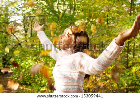 Side portrait view of a young african american black teenager walking through an autumn forest park and enjoying dry leaves falling on her during a sunny fall season day. - stock photo