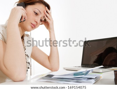 Side portrait view of a young professional business woman working on her accounts and looking at utility bills while calling and having a telephone conversation looking worried, interior. - stock photo