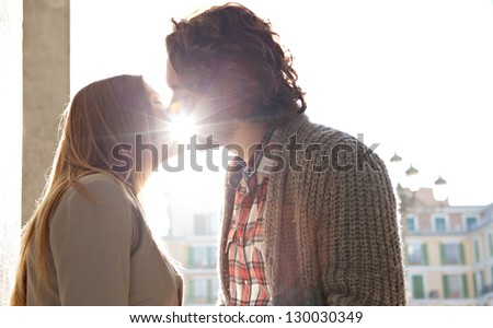 Side portrait view of a young romantic couple kissing while on vacation in a destination city, with the sun rays filtering through their lips. - stock photo
