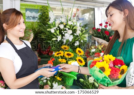 Side portrait view of an attractive shopper woman customer buying and paying with a credit card at a small florist business store and the shop attentant taking payment from credit card, outdoors. - stock photo