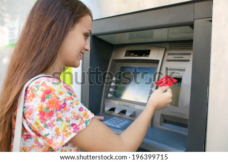 Side portrait view of an attractive young woman using a cash machine to withdraw cash money with her credit card, smiling in a city street. Outdoors finance and lifestyle.