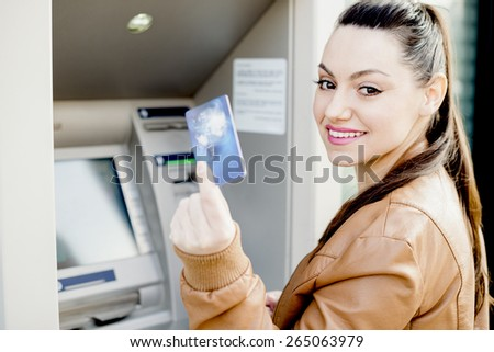 Side portrait view of an attractive young woman using a cash machine to withdraw cash money with her credit card, turning and smiling in a city street. Outdoors finance and lifestyle. - stock photo