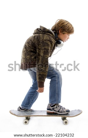 side pose of little boy riding skateboard against white background - stock photo