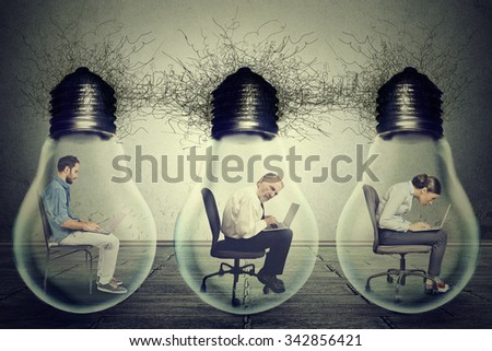 Side profile company employees sitting in row inside electric lamp light bulb using laptop isolated on gray office wall background. Idea exchange network concept. Working conditions productivity