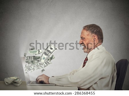 Side profile happy smiling business man working online on computer earning money dollar bills banknotes flying out of laptop screen isolated grey wall office background. Human face expression