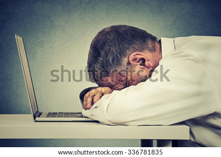 Side profile mature business man sleeping on a laptop isolated on grey office wall background. Sleep deprivation, long working hours concept - stock photo
