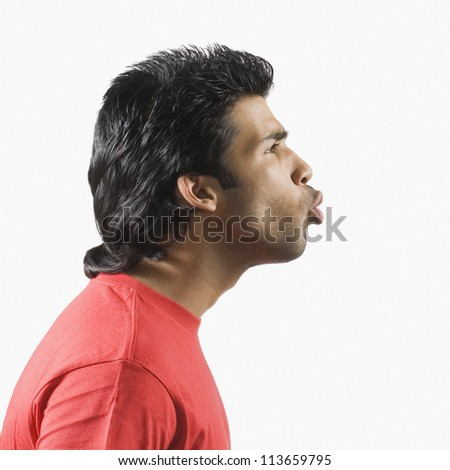 Side profile of a man puckering - stock photo