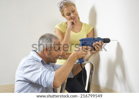 Side profile of a mid adult man drilling into a wall with a young woman standing beside him - stock photo