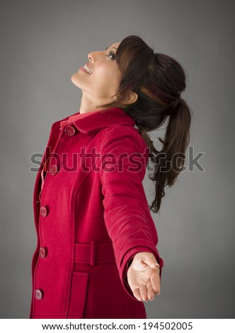 Side profile of an Indian young woman with arms outstretched and day dreaming - stock photo