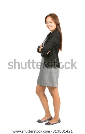 Side profile of engaging, charming, natural Asian businesswoman in casual black jacket, gray dress, arms crossed warmly smiling at camera. Thai national of Chinese origin.  - stock photo