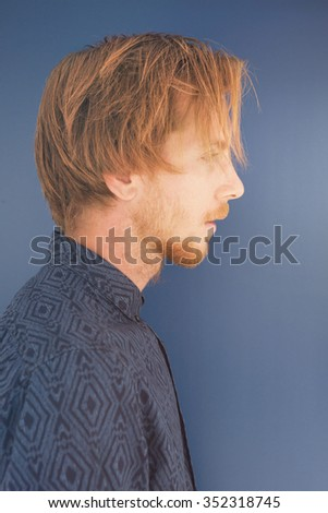 side profile of red-haired young man with beard