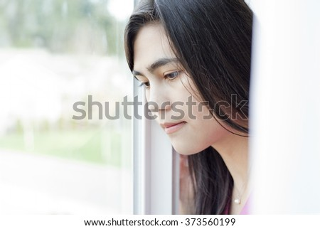 Side profile of teen girl or young woman looking out sunny window, sad or lonely expression - stock photo