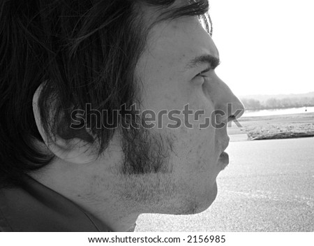 Side profile of young man.  Street in background. - stock photo