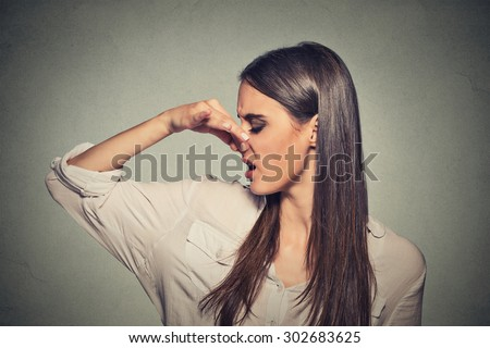 Side profile portrait headshot woman pinches nose with fingers looks with disgust away something stinks bad smell situation isolated gray wall background. Human face expression body language reaction  - stock photo