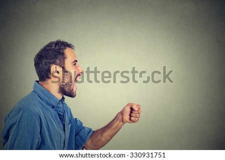Side profile portrait of a angry young man screaming with fist up in air isolated on gray wall background  - stock photo