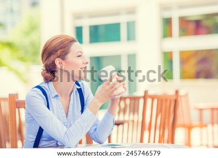 Side profile portrait young smiling woman drinking coffee outside corporate office isolated city building background coffee shop. Positive human face expression, emotion, life success, leisure concept - stock photo