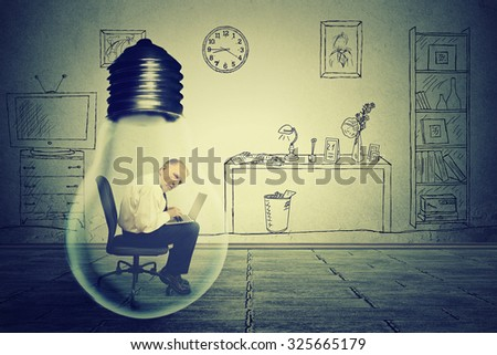 Side profile senior man using working on computer sitting inside electric lamp in his corporate office on a gray wall background. Generate idea concept  - stock photo