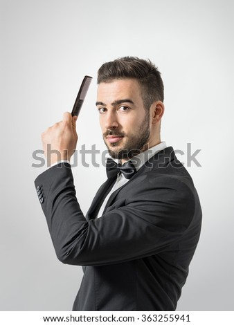 Side profile view of young man combing hair looking at camera. Desaturated portrait over gray studio background with retro vignette.  - stock photo