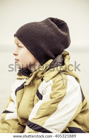 Side profile view on serious little boy in hat and thick winter coat looking away with obscured lake in background - stock photo