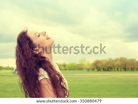 Side profile woman smiling looking up to blue sky celebrating enjoying freedom. Positive emotion face expression life perception success, peace of mind concept. Free happy girl  - stock photo