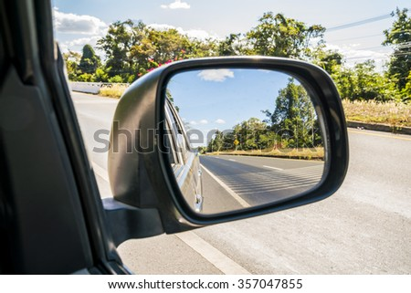 Side rear mirror of car show straight road - view of a road side of the car, Drive Thru, Traveling Theme  - stock photo
