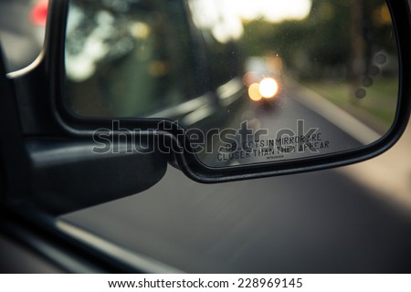 Side rear view mirror of a car on a road with out of focus reflections of the cars behind it (color toned image; shallow DOF) - stock photo