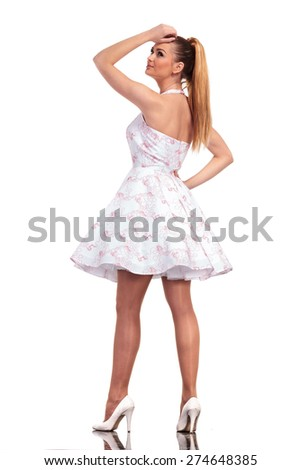 Side rear view of a elegant young woman looking up while holding her hand on her head. - stock photo