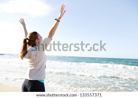 Side rear view of a young sporty woman stretching her arms up while standing on a beach by the shore and against a blue sky.