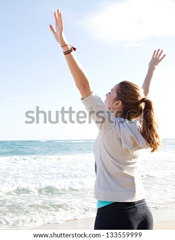 Side rear view of a young sporty woman stretching her arms up while standing on a beach by the shore and against a blue sky. - stock photo