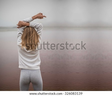 Side rear view of a young sporty woman stretching her arms up while standing on a beach by the shore and against a gray sky. Dirty red toxic water in lake. ecological catastrophe - stock photo
