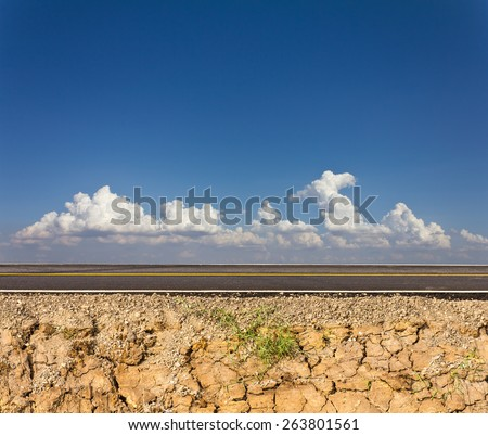 Side road in the countryside with cracked soil below and cloudy sky in the background. - stock photo