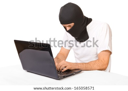 Side shot of man in black mask looking at monitor and typing something