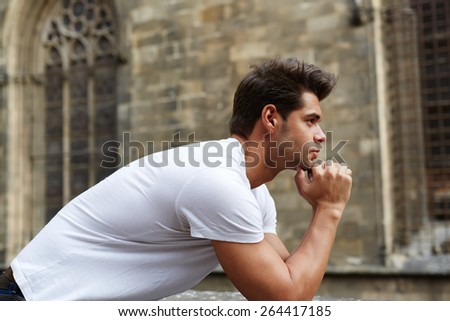 Side shot portrait of handsome man resting chin on clasped hands, confident man thinking about his choice, pensive man standing against gothic building - stock photo