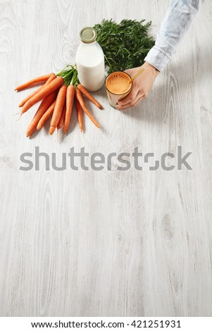 Side top view on wooden table, farm carrot harvest lying near bottle and man hand holds glass filled with mix natural fresh juice and milk with golden drinking straw in it,for breakfast in cafe - stock photo