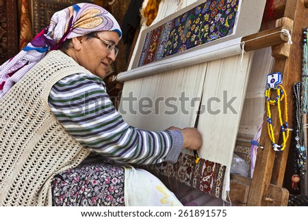 SIDE, TURKEY - MARCH 9, 2015: Unidentified female weaver knotting a handmade carpet at the shopping area in the town of Side. - stock photo