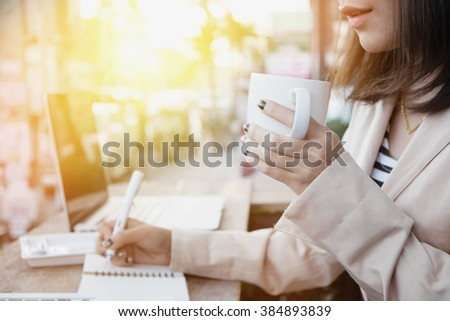 Side view and Close up business woman holding cup of coffee in morning time,vintage photo,Selective focus on hand. - stock photo