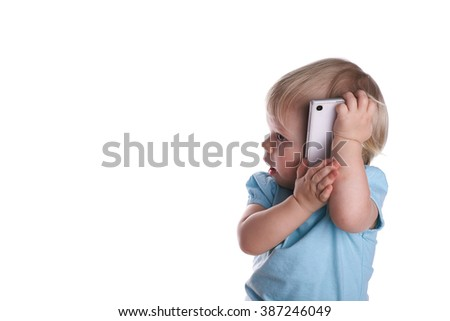Side view at happy little baby surprised in a blue t-shirt plays with mobile phone, isolated on a white, studio shot - stock photo